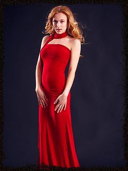 Wearing stylish red dress that hugs her body curves, her...