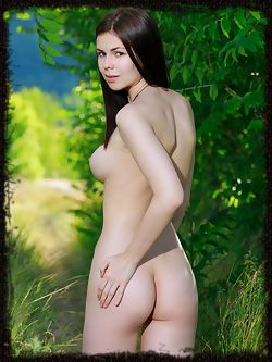 Karolina Young posing in the lush green woods. The deep...
