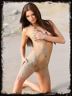 Anastacia, wet and naked in a sandy desolate beach...