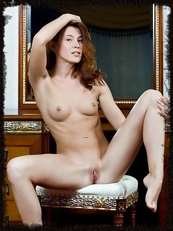 Kira J poses erotically on top of the bed, highlighting her...